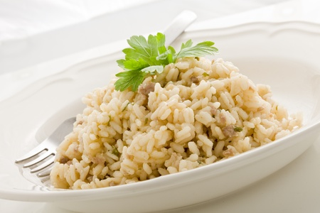 risotto: delicious italian risotto dish with meat and parsley on white isolated background