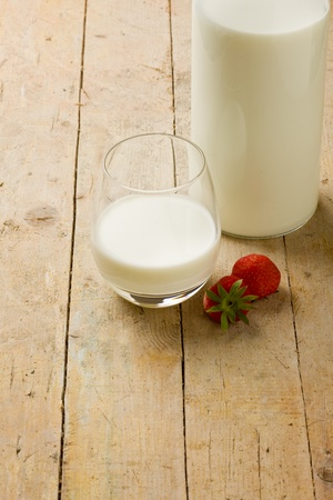 cup of milk with strawberry on wooden table photo