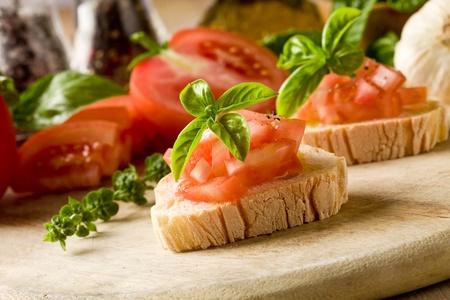 basilico: deliciosa bruschetta con tomates en mesa de madera  Foto de archivo