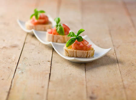 delicious bruschetta with tomatoes on wooden table Stock Photo - 9960770