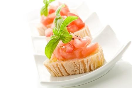 ajo:  deliciosa bruschetta con tomates en mesa de madera sobre el fondo aislado Foto de archivo