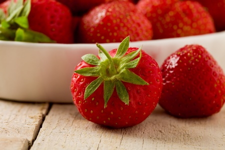 delicious red strawberries on wooden table photo