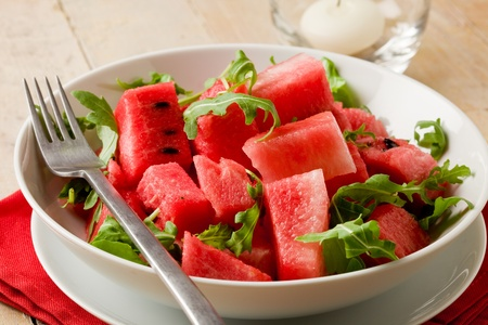 delicious fresh watermelon and arugula salad on wooden table photo