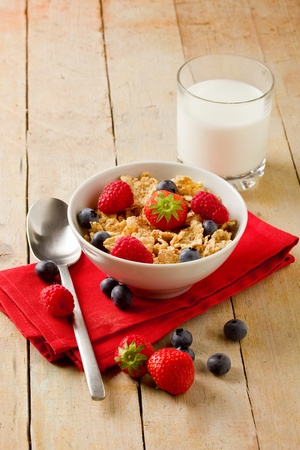 delicious breafast made of corn flakes with berries and fresh milk photo