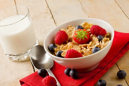 delicious breakfast made of corn flakes with berries and fresh milk photo