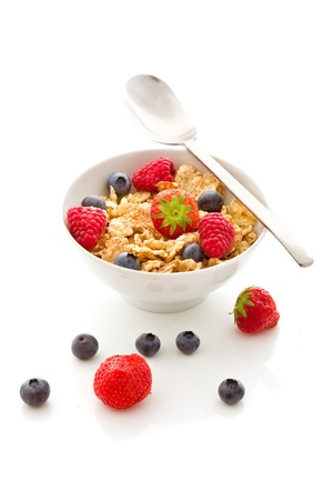 crystal bowl: delicious breakfast isolated on white made of corn flakes with berries and fresh milk