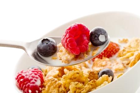 delicioso desayuno aislado en blanco de copos de maíz con bayas y leche fresca