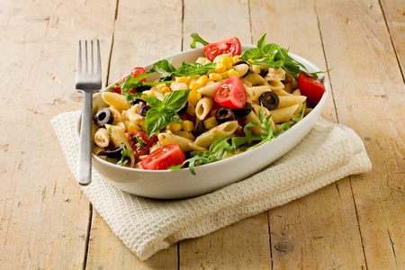 corn salad: photo of delicious tasty pasta salad on wooden table with fresh vegetables