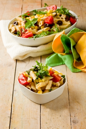 photo of delicious tasty pasta salad on wooden table with fresh vegetables photo