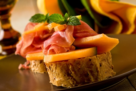 bruschetta: photo of tasty bread slices with bacon and melon  Stock Photo
