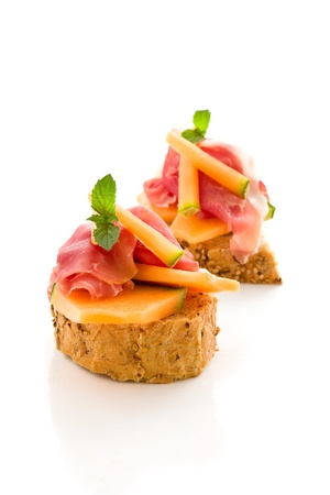 canapes: photo of tasty bread slices with bacon and melon on isolated background Stock Photo