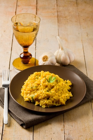 delicious risotto with saffron on wooden table with garlic and napkin