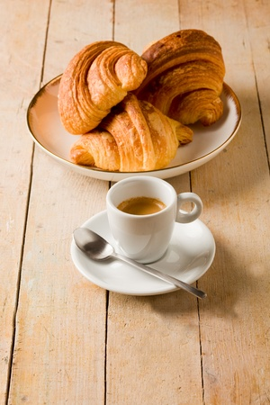 photo of fresh coffee and croissants on brown wooden table photo