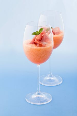photo of delicious ham and melon cocktail appetizer on light blue background photo