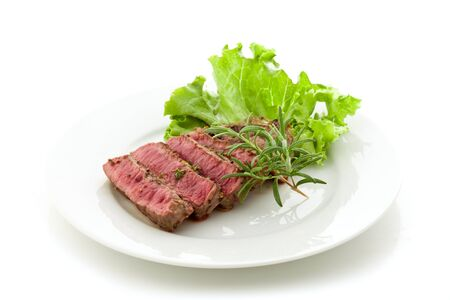 photo of delicious and pefect cooked beaf steak with rosemary and lettuce photo