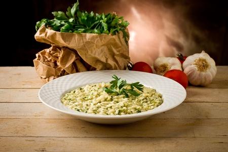 espinacas: foto de delicioso plato risotto a las hierbas en la mesa de madera
