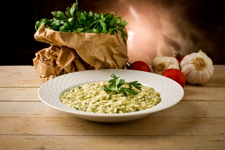 risotto: photo of delicious risotto dish with herbs on wooden table