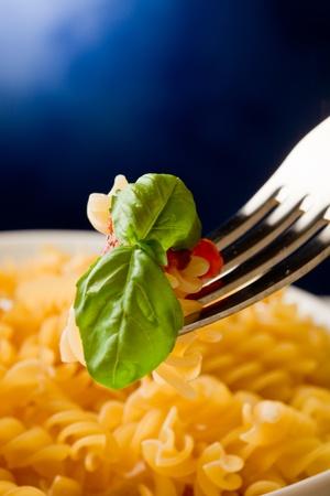 foglia: photo of delicious pasta with tomato sauce on blue background