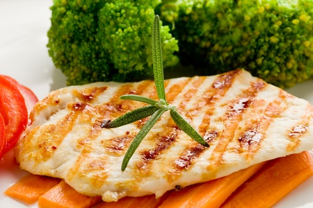 photo of delicious grilled chicken breast with various vegetables