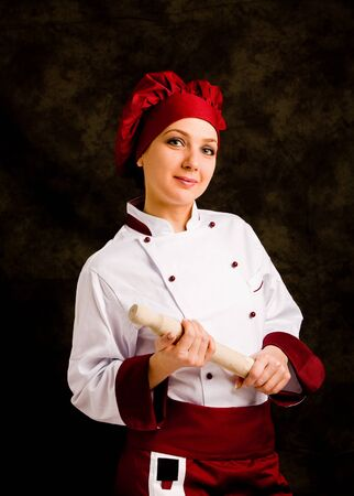 successfull: photo of young successfull female chef with rolling pin in her hands