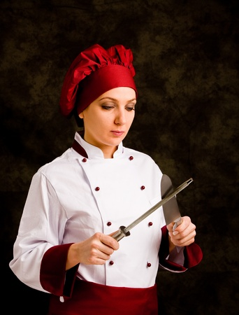 photo of female chef with kinife and sharpener on rural background Stock Photo - 10951688