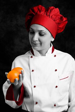 photo of young female chef controlling orange quality photo