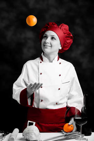 photo of female chef juggling with orange on dark rural background photo