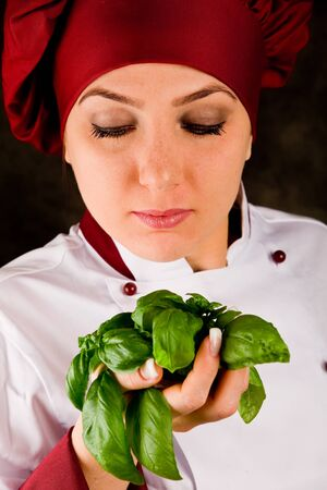 photo of young female chef controlling basil quality photo