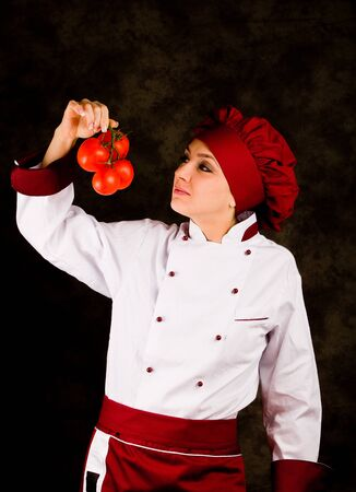 photo of young female chef controlling tomato quality photo