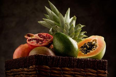 canastas con frutas: foto de cesta llena de deliciosas frutas tropicales, frente a un entorno rural