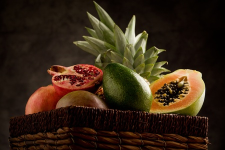 photo of basket full with delicious tropical fruits in front of a rural background photo