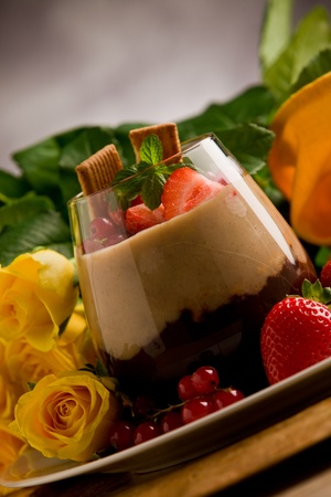 chocolate hazelnut mousse with berries in front of a rose background photo