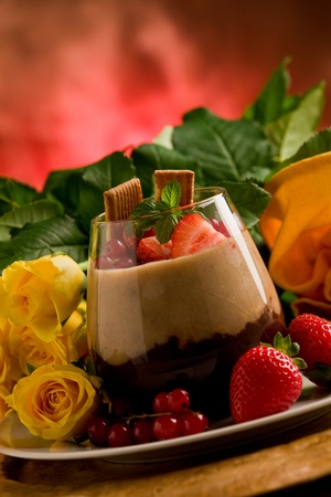 chocolate hazelnut mousse with berries in front of a rose background