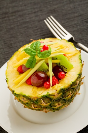 papaya: photo of delicious pineapple dessert stuffed with tropical fruits