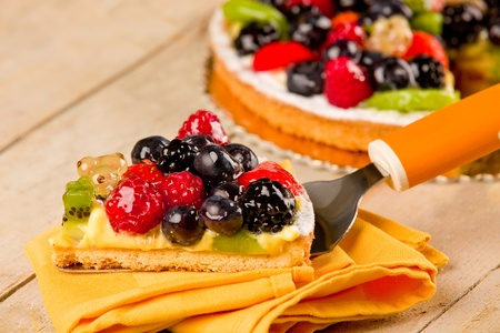 photo of delicious pie with various fruits on wooden table photo