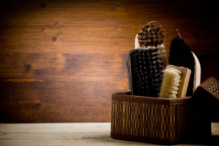 photo of various brushes on wooden table used for polishing shoes  Stock Photo