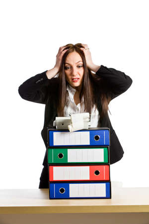 office chaos: photo of young woman with binder pile holding her smoking head on white Stock Photo