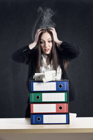 photo of young woman with binder pile holding her smoking head photo