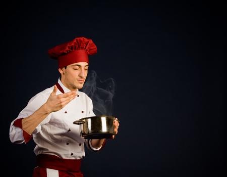 photo of young chef with pot in his hend tasting the food smell photo