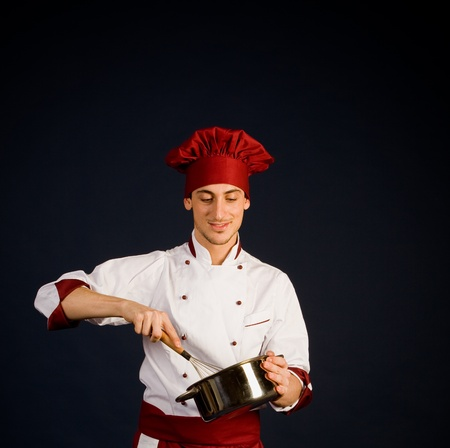 photo of young male chef with a pot in his hand who is cooking photo