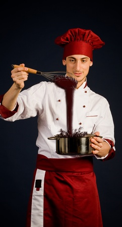 liquid chocolate: photo of young chef with pot who is preparing chocolate Stock Photo