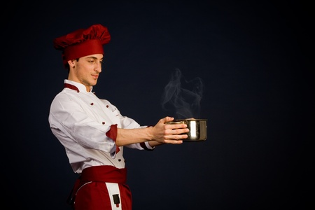 photo of young chef holding a hot pot in his hand photo