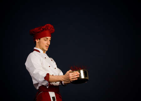 photo of young chef holding careless a pot with tomato sauce photo