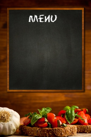 photo of blackboard with bruschetta appetizer background on wooden wall Stock Photo