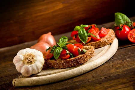 bruschetta: photo of delicious bruschetta appetizer with fresh cutted tomatoes and basil