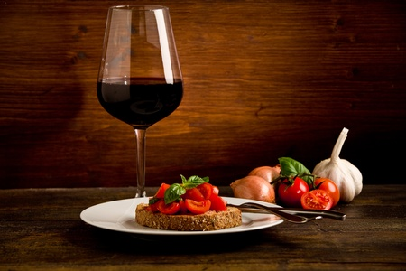 sicilian: photo of delicious bruschetta appetizer with red wine glass on wooden table Stock Photo