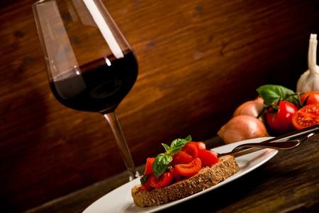 bread and wine: foto de la deliciosa bruschetta aperitivo con un vaso de vino tinto en la mesa de madera Foto de archivo