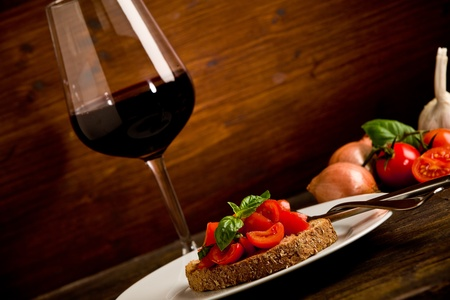 photo of delicious bruschetta appetizer with red wine glass on wooden table photo