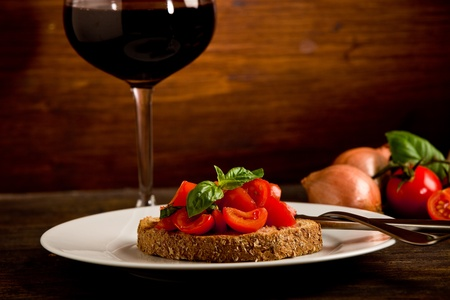 wine and food: photo of delicious bruschetta appetizer with red wine glass on wooden table Stock Photo