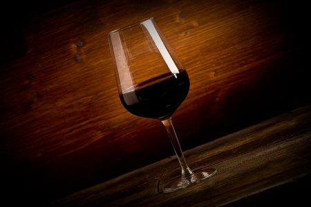 photo of delicious dark red wine goblet on wooden table illuminated by spot photo